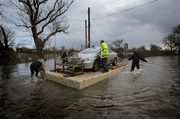 Men use a pontoon to move a car in floodwaters in England. More Photos of the Day: http://t.co/FRtR4mSIQM (Getty) http://t.co/QeaNAsRj0r - embedded image