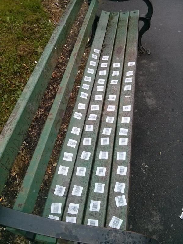 Someone was bored. (Bench covered with bar code stickers)  - embedded image